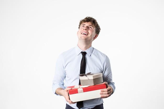 Junger schöner mann in bürokleidung mit geschenken