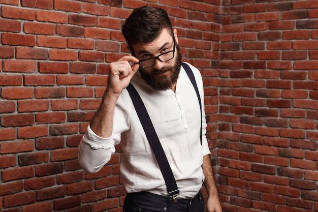 Junger schöner mann in den gläsern auf ziegelmauer.
