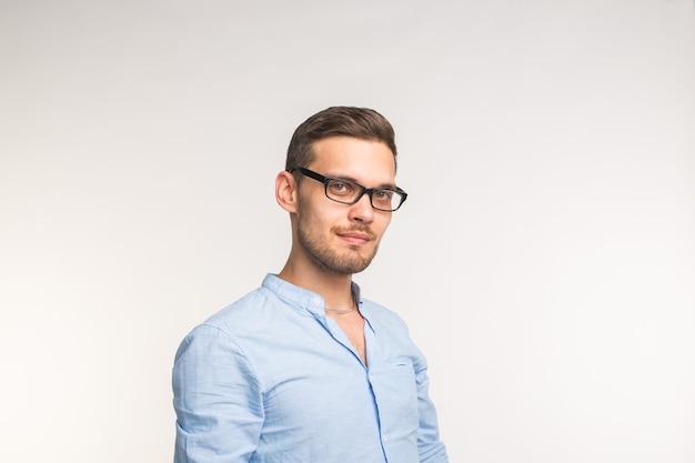 Junger schöner mann in den gläsern, die lokalisiert auf weißem hintergrund lächeln