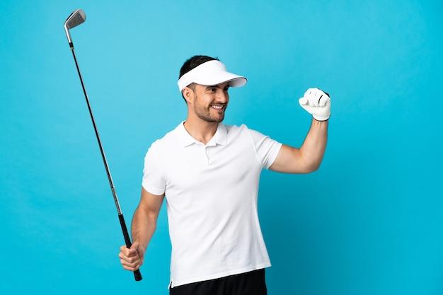Junger schöner mann lokalisiert auf blauem hintergrund, der golf spielt und einen sieg feiert