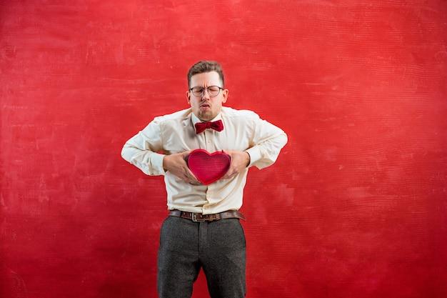 Junger schöner mann mit abstraktem herzen auf rotem studiohintergrund