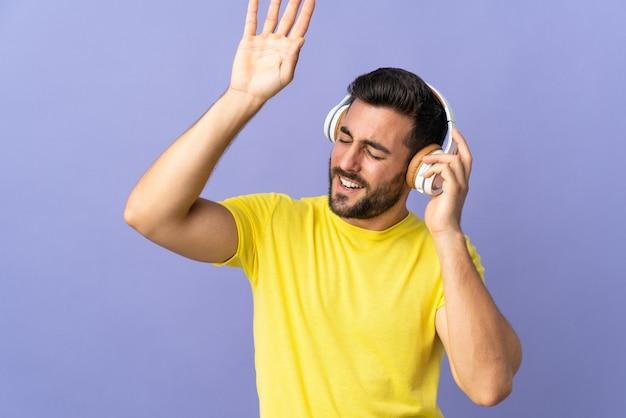 Junger schöner mann mit bart lokalisiert auf lila hörende musik und tanzend