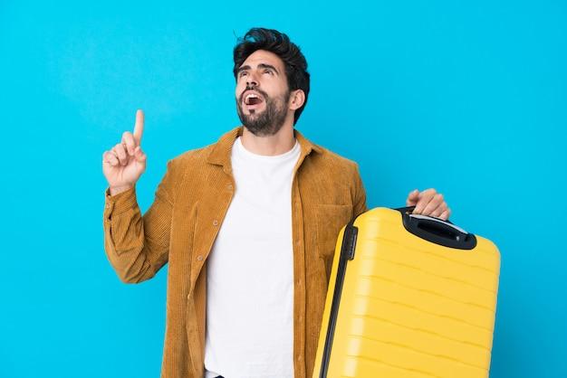 Junger schöner mann mit bart über isolierter blauer wand im urlaub mit reisekoffer und nach oben zeigend