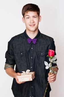 Junger schöner mann mit blume und geschenk.