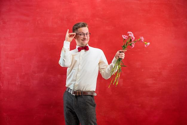 Junger schöner mann mit blumen auf rotem studiohintergrund