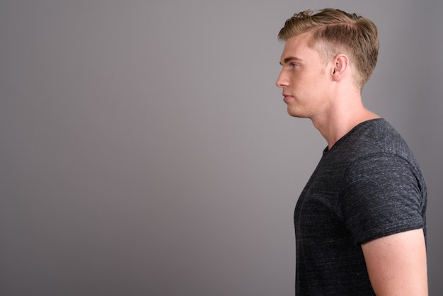 Junger schöner mann mit dem blonden haar, das graues hemd auf grauer wand trägt