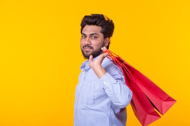 Junger schöner mann mit einem bart hält rote einkaufstaschen, die auf einer gelben wand aufwerfen
