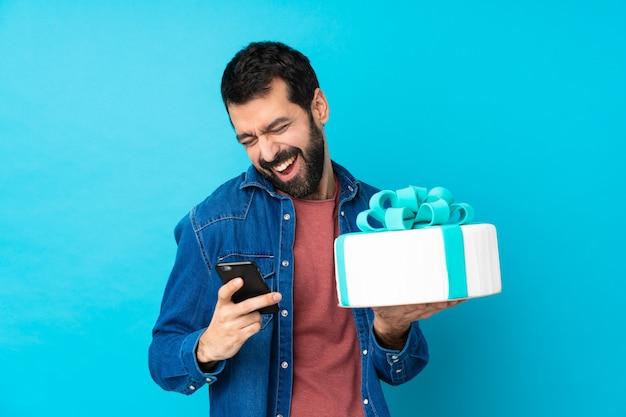 Junger schöner mann mit einem großen kuchen mit telefon in der siegposition