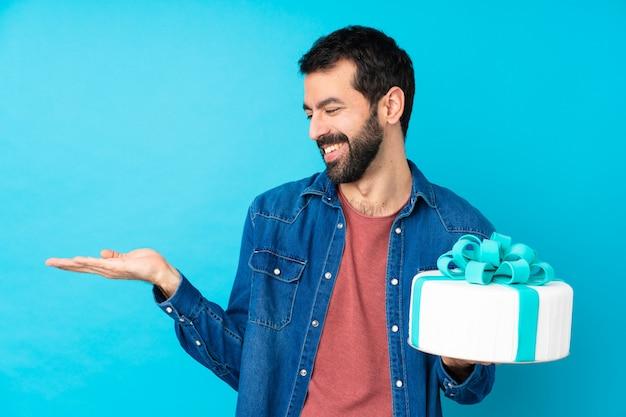 Junger schöner mann mit einem großen kuchen über der blauen wand, die leerzeichen mit zwei händen hält