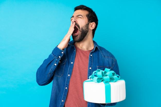 Junger schöner mann mit einem großen kuchen über isoliertem blau