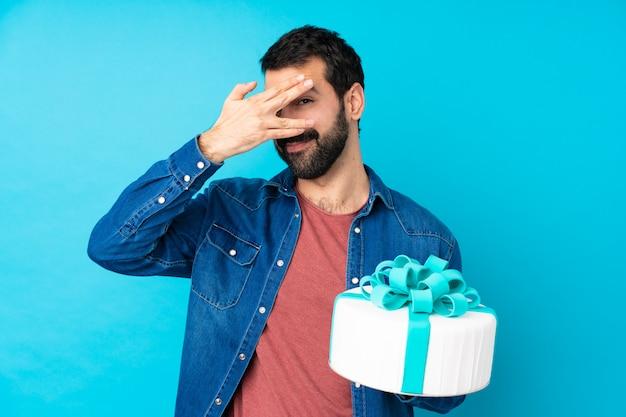 Junger schöner mann mit einem großen kuchen über isolierter blauer wand, die augen durch hände bedeckt und lächelt