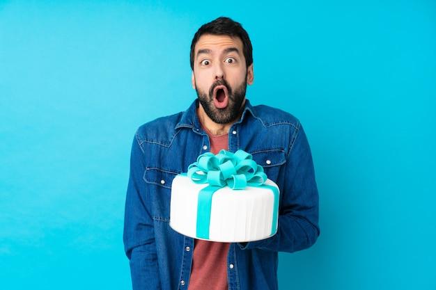 Junger schöner mann mit einem großen kuchen über isolierter blauer wand mit überraschendem gesichtsausdruck