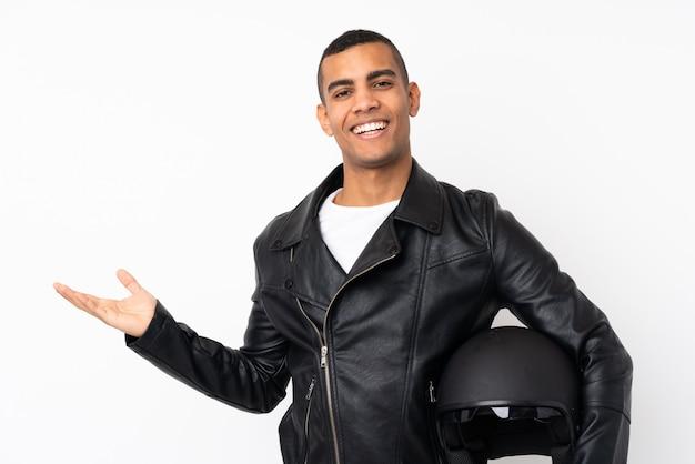 Junger schöner mann mit einem motorradhelm über isolierter weißer wand, die imaginären copyspace auf der handfläche hält