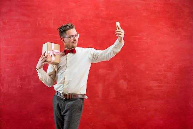Junger schöner mann mit geschenk und telefon