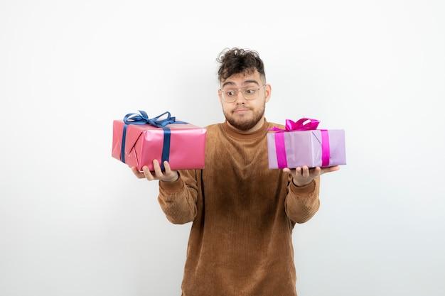 Junger schöner mann mit geschenkboxen stehend und posierend.