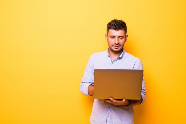 Junger schöner mann mit laptop auf gelbem hintergrund