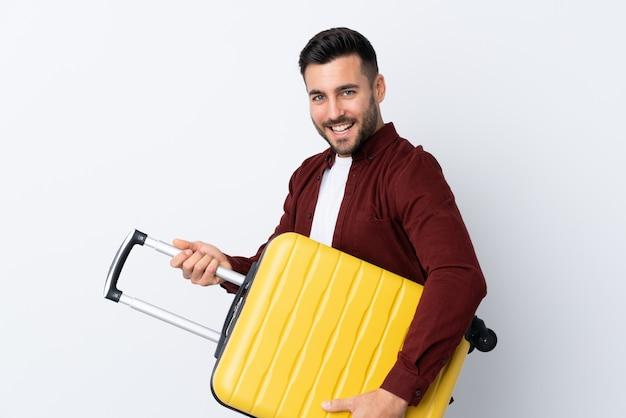 Junger schöner mann über isolierter weißer wand im urlaub mit reisekoffer