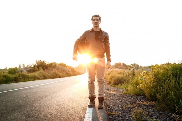 Junger schöner motorradfahrer, der helm hält und an landstraße aufwirft.