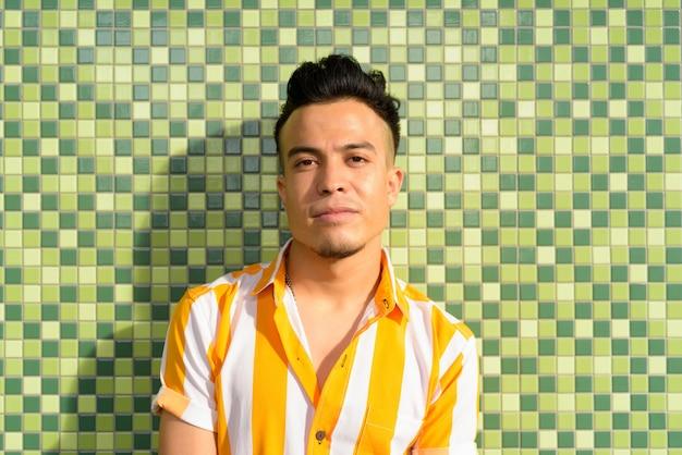 Junger schöner multiethnischer mann gegen grünen hintergrund