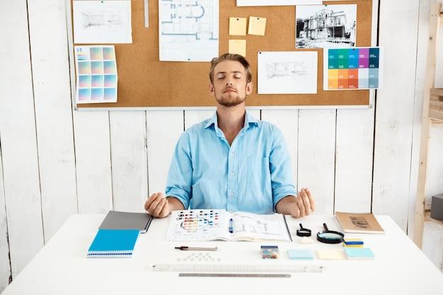 Junger schöner nachdenklicher entspannter geschäftsmann, der meditierend am tisch meditiert. weiße moderne büroeinrichtung.
