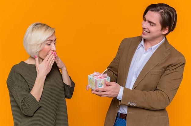 Junger schöner paar glücklicher mann, der seiner schönen überraschten freundin ein geschenk gibt, das in der liebe zusammen glücklich ist
