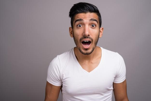 Junger schöner persischer mann gegen grauen hintergrund