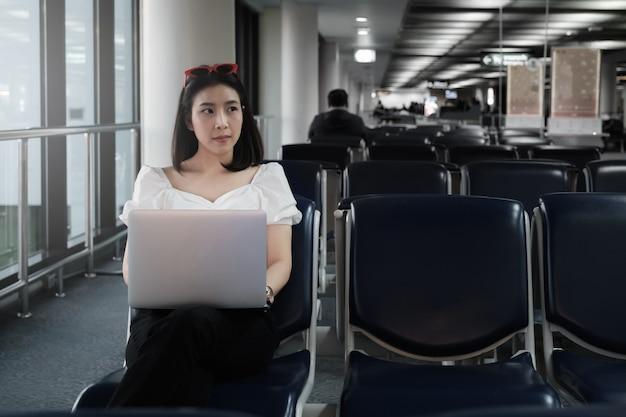Junger schöner reisender und leere stühle in der abflughalle am flughafen mit laptop.
