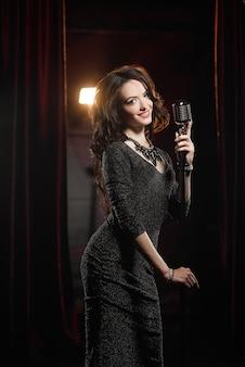 Junger schöner sänger im schwarzen kleid, das mit mikrofon aufwirft