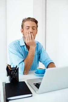 Junger schöner schläfriger, selbstbewusster, nachdenklicher geschäftsmann, der am tisch sitzt und am laptop mit tasse kaffee beiseite arbeitet. weiße moderne büroeinrichtung