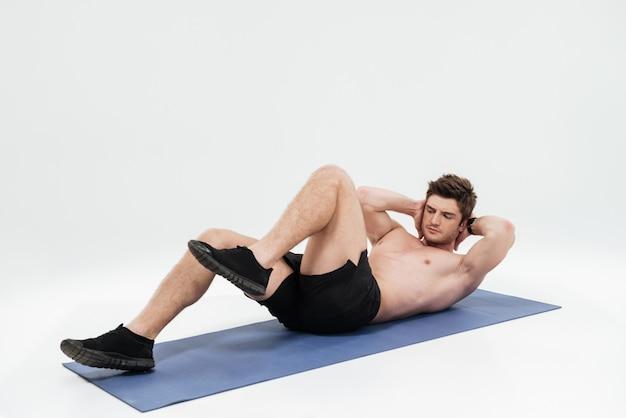 Junger schöner sportler, der beinübungen auf einer fitnessmatte tut