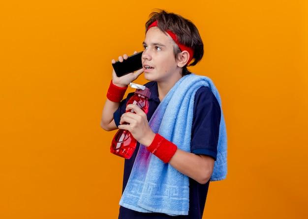 Junger schöner sportlicher junge, der stirnband und armbänder mit zahnspangen und handtuch auf schulter hält wasserflasche hält, die am telefon spricht, das gerade lokalisiert auf orange wand mit kopienraum schaut
