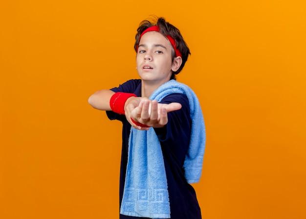 Junger schöner sportlicher junge, der stirnband und armbänder mit zahnspangen und handtuch auf schulter trägt, die in der profilansicht lokalisiert auf orange wand stehen