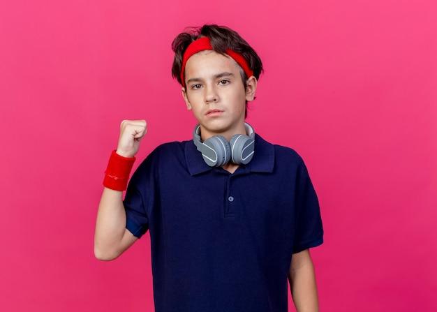 Junger schöner sportlicher junge, der stirnband und armbänder und kopfhörer am hals mit zahnspangen trägt, die kamera betrachten, die hinter lokalisiert auf purpurrotem hintergrund mit kopienraum zeigt