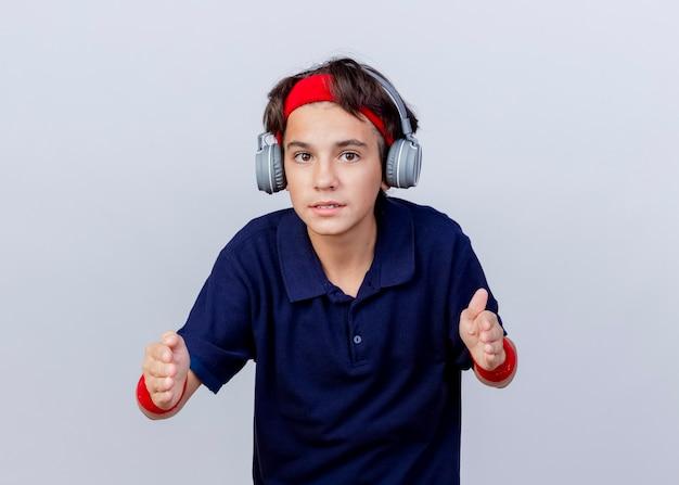 Junger schöner sportlicher junge, der stirnband und armbänder und kopfhörer mit zahnspangen trägt, die kamera betrachten, die größe lokalisiert auf weißem hintergrund mit kopienraum zeigt