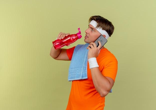 Junger schöner sportlicher mann, der stirnband und armbänder mit handtuch auf schulter spricht, die am telefon sprechen und wasserflasche lokalisiert auf olivgrünem hintergrund mit kopienraum halten