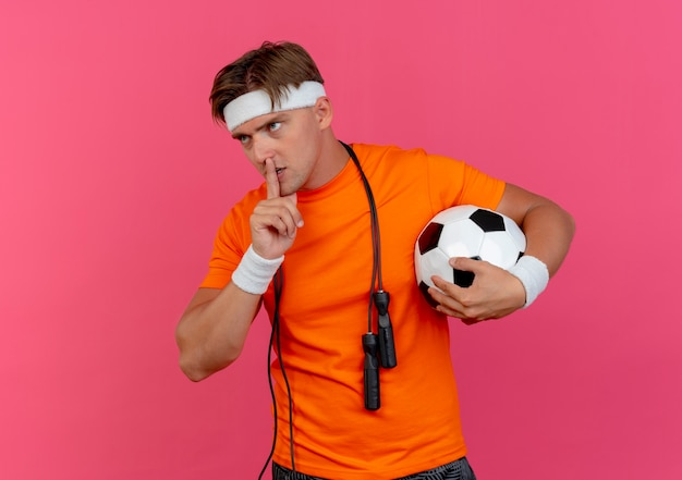Junger schöner sportlicher mann, der stirnband und armbänder mit springseil um hals hält, der fußball betrachtet, der seite betrachtet und stille gestikuliert, lokalisiert auf rosa hintergrund mit kopienraum