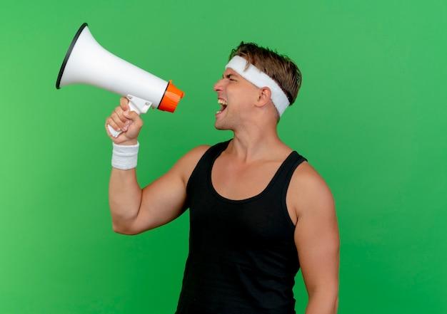 Junger schöner sportlicher mann, der stirnband und armbänder schreit, die im lauten lautsprecher lokalisiert auf grünem hintergrund mit kopienraum schreien
