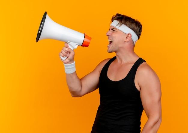Junger schöner sportlicher mann, der stirnband und armbänder schreit, die im lautsprecher lokalisiert auf orange hintergrund schreien