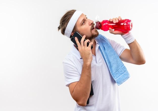 Junger schöner sportlicher mann, der stirnband und armbänder spricht, die am telefon sprechen und wasserflasche mit springseil und handtuch auf schultern lokalisiert auf weißem raum halten
