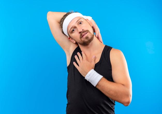 Junger schöner sportlicher mann, der stirnband und armbänder trägt, die arm um kopf und hand auf brust setzen lokalisiert auf blauem raum suchen