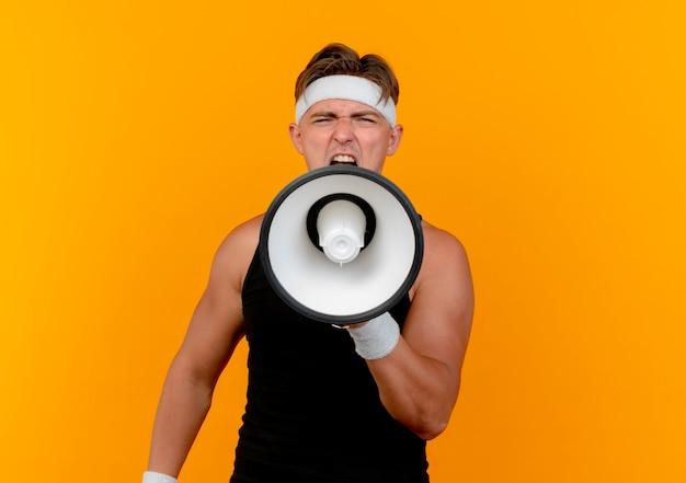 Junger schöner sportlicher mann, der stirnband und armbänder trägt, die im lautsprecher an der kamera lokalisiert auf orange hintergrund mit kopienraum schreien