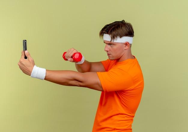 Junger schöner sportlicher mann, der stirnband und armbänder trägt, die in der profilansicht halten, die handy und hantel betrachtet, die telefon lokalisiert auf olivgrünem hintergrund mit kopienraum betrachtet