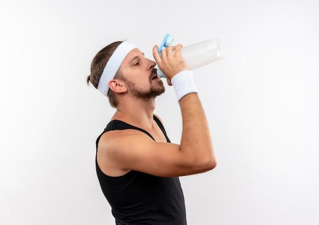 Junger schöner sportlicher mann, der stirnband und armbänder trägt, die in der profilansicht stehen und wasser von der flasche lokalisiert auf weißem raum stehen