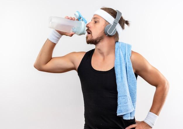 Junger schöner sportlicher mann, der stirnband und armbänder und kopfhörertrinkwasser von wasserflasche mit handtuch auf schulter und hand auf taille lokalisiert auf weißem raum trägt