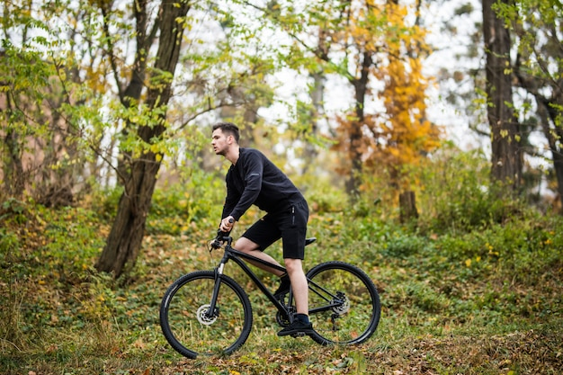 Junger schöner sportmann mit seinem fahrradtraining im park in der herbstzeit.