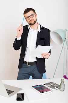 Junger schöner stilvoller hipster-mann in der schwarzen jacke, die am bürotisch, geschäftsstil, weißes hemd, isoliert, laptop, start, arbeitsplatz, denken, dokumente arbeitet