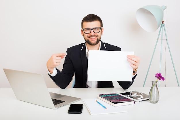 Junger schöner stilvoller hipster-mann in der schwarzen jacke, die am bürotisch, geschäftsstil, weißes hemd, isoliert, laptop, start, arbeitsplatz, denken, dokumente, zeigefinger auf papier arbeitet