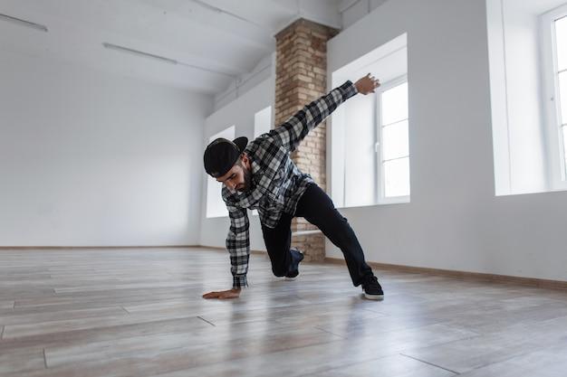 Junger schöner stilvoller tänzer mann mit einer kappe und lässigem kleid tanzen breakdance in der halle
