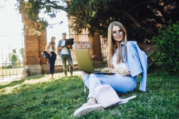 Junger schöner student, der auf dem gras auf dem campus sitzt
