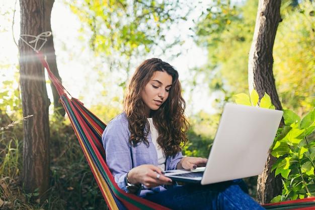 Junger schöner student, der auf einer hängematte im park sitzt und online mit einem laptop lernt